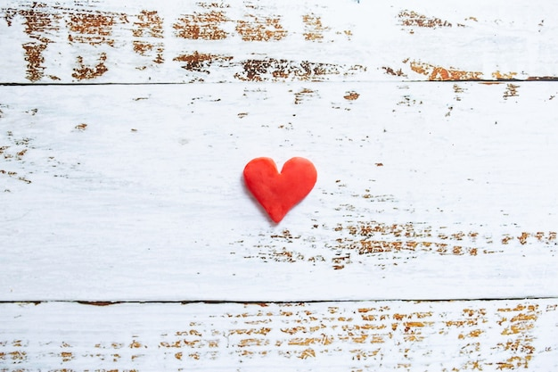 Cuore rosso di plastilina su fondo di legno bianco.