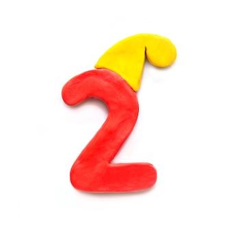 Numero rosso di plastilina due in cappello invernale giallo su sfondo bianco
