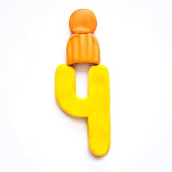 Plastilina giallo numero 4 quattro in cappello invernale arancione con pompon su sfondo bianco