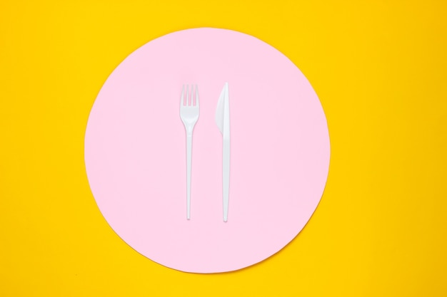 Plastick forchetta e coltello su sfondo giallo con cerchio rosa. vista dall'alto, minimalismo