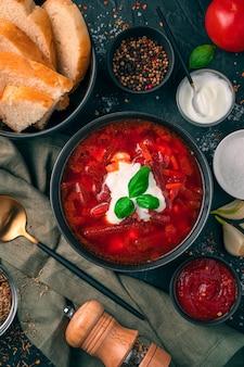 Un piatto di zuppa di barbabietole con panna acida e rosmarino, pane e salsa di pomodoro su uno sfondo di cemento nero. vista dall'alto, verticale.