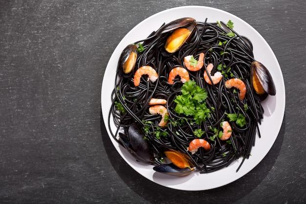 Piatto di spaghetti neri al nero di seppia con gamberi, cozze e prezzemolo sul tavolo scuro, vista dall'alto