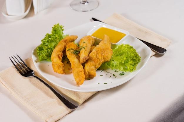 Piatto di bastoncini di pollo e salsa di immersione al coperto