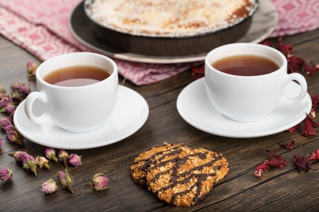 Piatto di torta al cocco, biscotti e tazze di tè caldo sulla superficie della pietra
