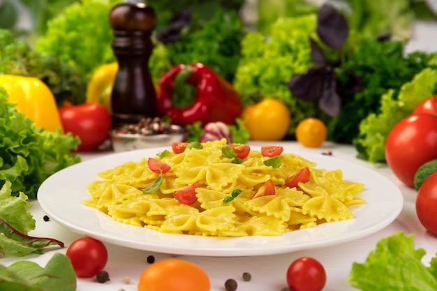 Piatto di pasta rigata italiana cotta con pomodori e foglie di basilico con molto cibo intorno food