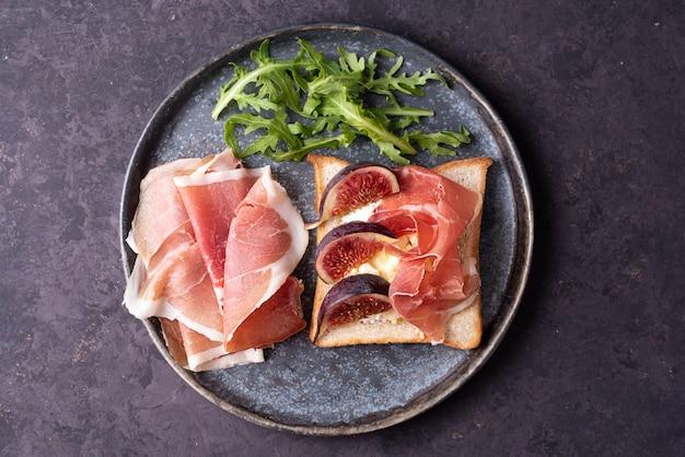 Piatto di crostini con prosciutto e fichi su un fondo di cemento grigio, toast con prosciutto italiano, antipasto con jamon.
