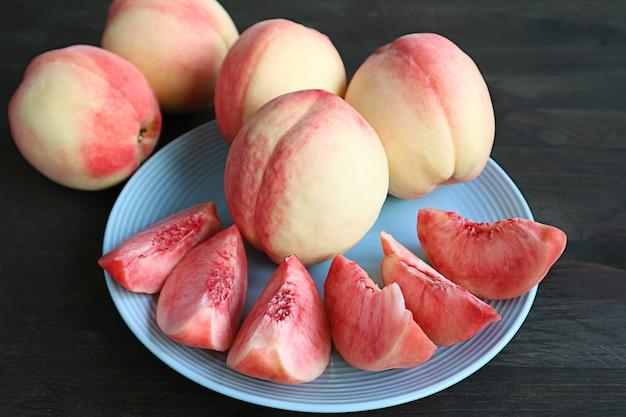 Piatto di pesche fresche e mature tagliate per dessert con frutta intera