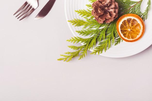 Piatto e posate decorati con ramoscello di conifere e arancia secca su fondo grigio chiaro.