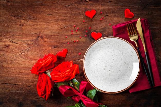 Piatto, posate e rose, concetto di cena romantica. spazio libero per il testo