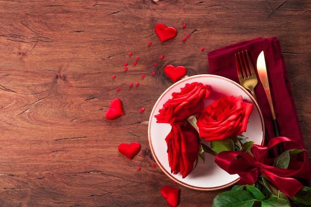 Piatto, posate e rose, concetto di cena romantica