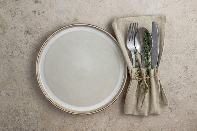 Piatto e posate con tovagliolo di lino su sfondo di pietra beige tavola rustica in colori caldi naturali vista dall'alto
