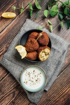 Piatto di delizioso piatto di falafel con salsa allo yogurt sul tavolo