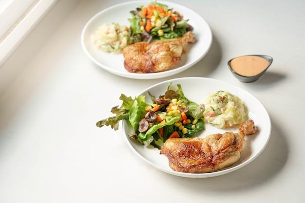 Piatto di deliziosa bistecca di cosce di pollo alla griglia con verdure e insalata di patate su bianco