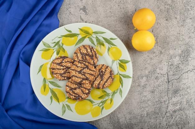 Piatto di deliziosi biscotti di farina d'avena e limoni freschi su pietra.