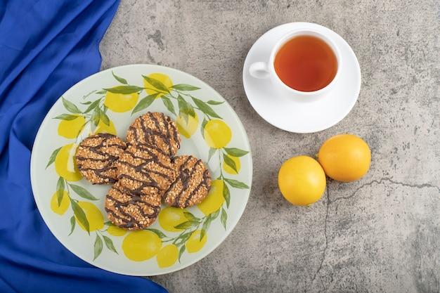 Piatto di deliziosi biscotti di farina d'avena con tè e limone su pietra.