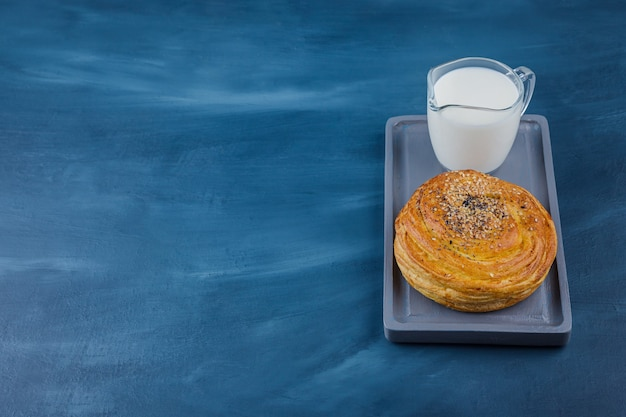 Piatto di deliziosa pasticceria con semi neri e bicchiere di latte sulla superficie blu.