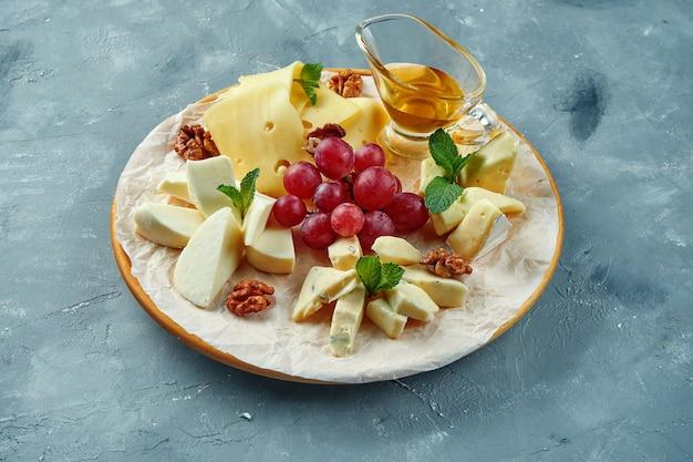 Un piatto di diversi formaggi serviti con uva, noci e miele. antipasto piatto di formaggi. tagliata di camembert, brie, gorgonzola