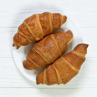 Piatto di croissant appena sfornati sulla vista superiore del tavolo in legno bianco