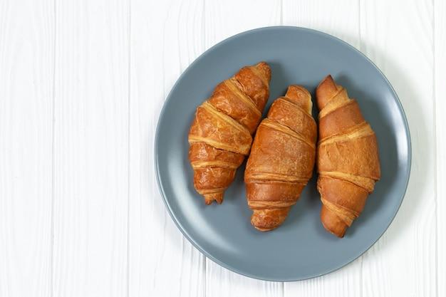 Piatto di croissant appena sfornati sulla vista dall'alto del tavolo in legno bianco
