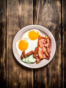 Piatto di uova fritte, pancetta, cetriolo e salsicce affumicate su un tavolo di legno