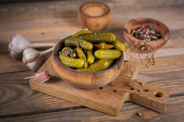 Piatto di cetriolini, cetrioli sottaceto su un fondo di legno rustico. mangiare pulito, concetto di cibo vegetariano