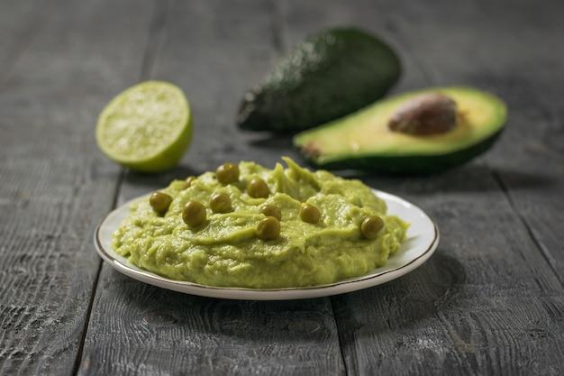 Un piatto di guacamole con piselli e avocado su un tavolo di legno. dieta vegetariana cibo messicano avocado. cibo crudo.