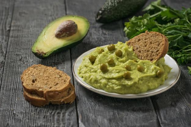 Un piatto di guacamole con piselli, pane e avocado su un tavolo di legno. dieta vegetariana cibo messicano avocado. cibo crudo.