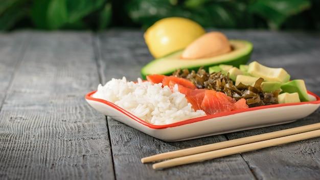 Un piatto di riso hawaiano, avocado, salmone e alghe e salsa di soia.
