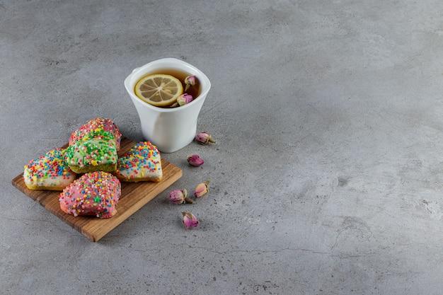 Un piatto di biscotti a forma di cuore con spruzza e una tazza di tè caldo.