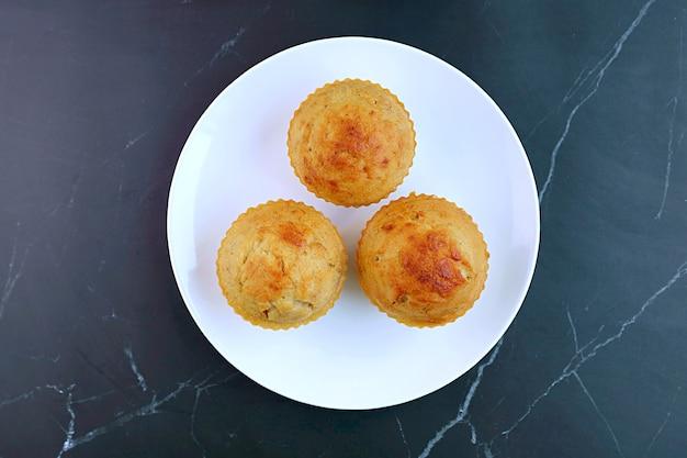 Piatto di muffin fatti in casa alla banana sul tavolo di pietra di marmo nero