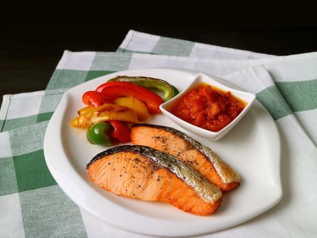 Piatto di bistecche di salmone alla griglia fatti in casa con verdure colorate