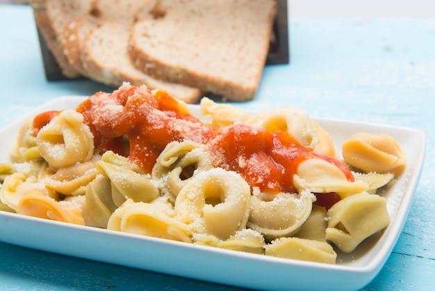 Piatto di tortellini italiani con formaggio grattugiato servito sul tavolo