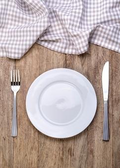 Piatto, coltello e forchetta su legno