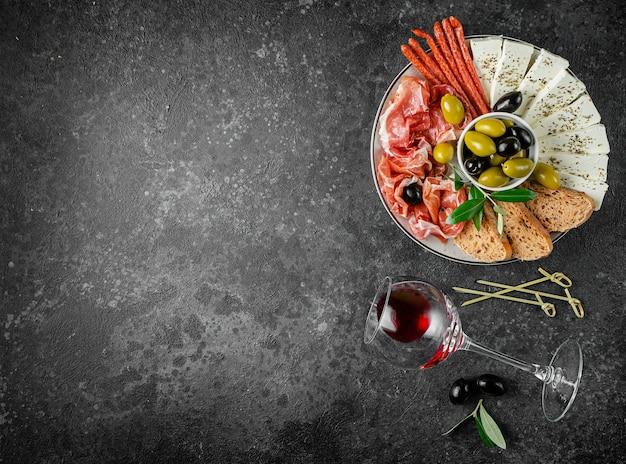 Piatto di spuntini di antipasti mediterranei con vino rosso su una superficie di cemento. lay piatto, copia spazio, overhead.