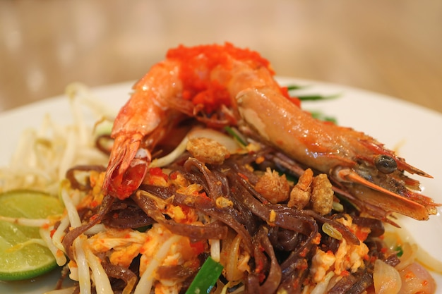 Piatto di pad thai o thai style noodle saltati in padella condita con gamberetti interi