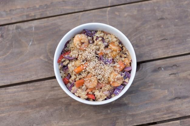 Piatto di paella con gamberetti, riso e verdure sulla tavola di legno marrone. prendi le spese generali