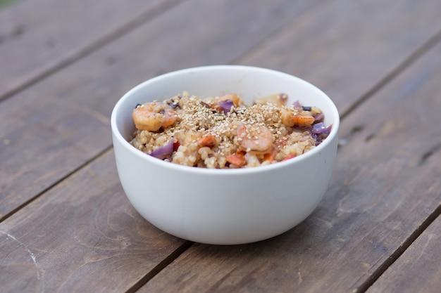 Piatto di paella con gamberetti, riso e verdure sulla tavola di legno marrone.