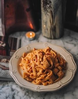 Un piatto di pasta con panna e pancetta