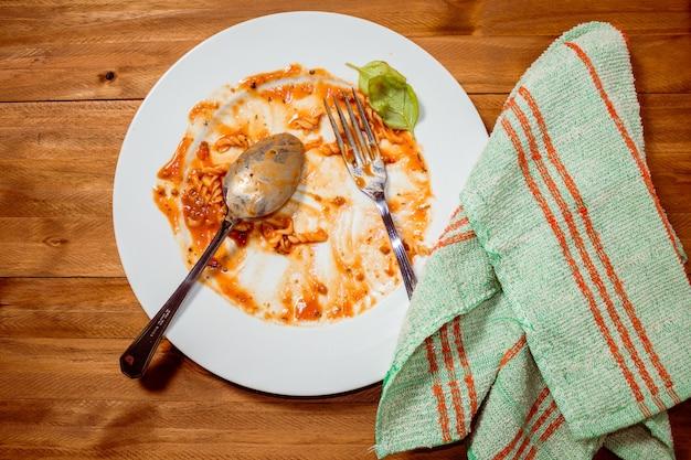 Piatto di pasta al sugo finito e sporco su un tavolo di legno. vista dall'alto