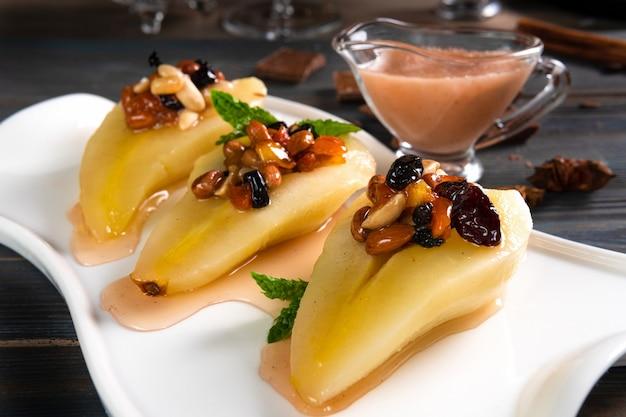 Un piatto di dessert di pere con salsa di vino su un tavolo di legno scuro