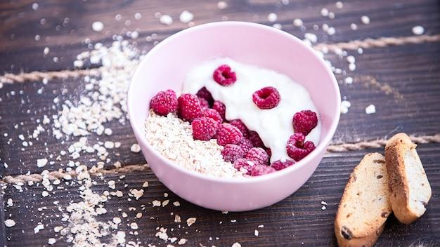 Un piatto di porridge e lamponi con pangrattato si trova su un tavolo di legno grezzo. concetto di salute. focalizzazione morbida.