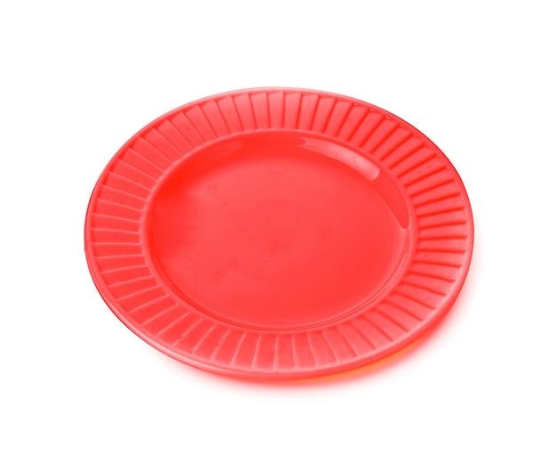 Piatto rosso vuoto su sfondo bianco