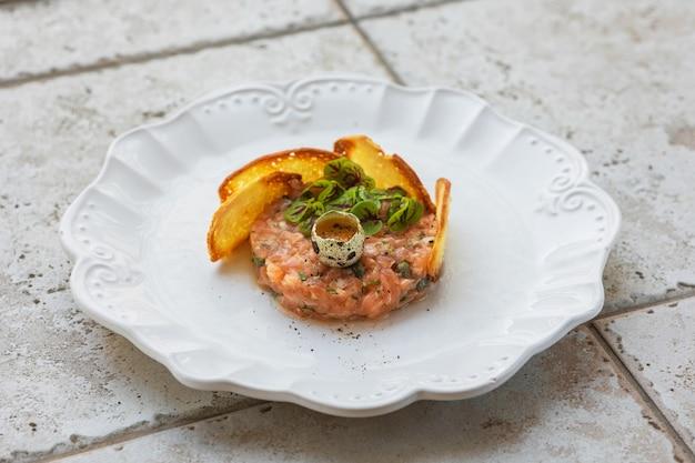 Piatto di tartare di salmone con uovo crudo e fette di pane tostato