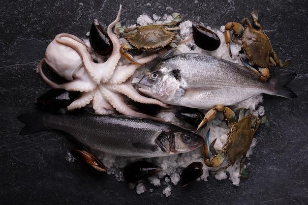 Piatto di frutti di mare con seppie fresche, cozze, granchio blu, branzino e pesce dorado su ghiaccio