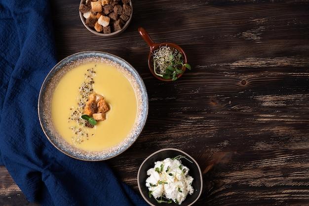 Piatto di zuppa di crema di zucca con crostini, formaggio e microgreens su uno sfondo di legno scuro, zuppa di purea vegetariana sana.