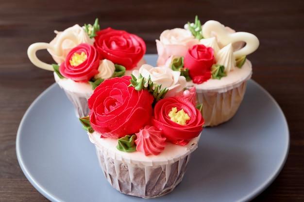 Piatto di stupendi cupcakes glassati a forma di bouquet di fiori su sfondo marrone scuro