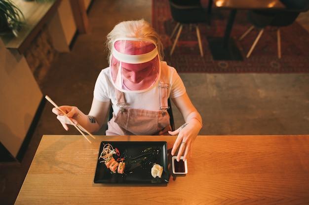 Piatto di rotoli di sushi nel ristorante con la donna che tiene le bacchette