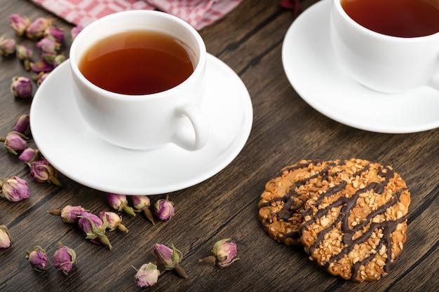 Piatto di torta dolce con granelli di cocco, biscotti e tazza di tè su una superficie di legno