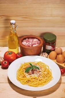 Piatto di gustosi spaghetti con salsa di pomodoro e carne su un tavolo di legno.