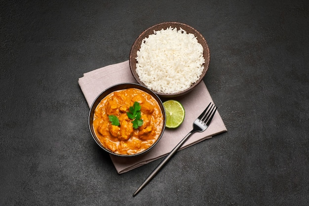 Piatto di tradizionale pollo al curry e riso sul tavolo scuro